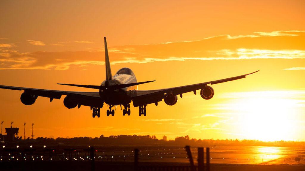 Flygplan landar i solnedgång